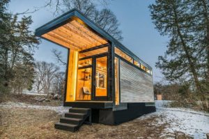 going tiny house with lights on in wilderness